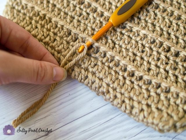 Insert your hook down into the free loop and grab the center of the fringe with your crochet hook.