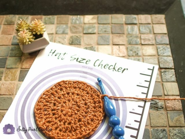 Photo of a flat circle hat crown on the crochet hat size checker, ready to be turned into a hat.f