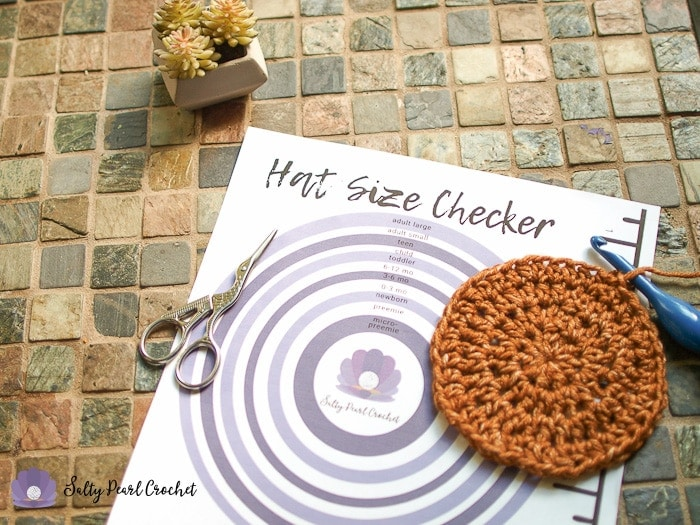 A closeup shot of a printed crochet hat size chart by age on the Hat Size Checker Printable.