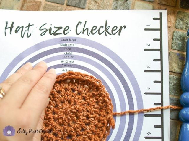 Using the Crochet Hat Size Checker Printable to determine the size this crochet hat will be.