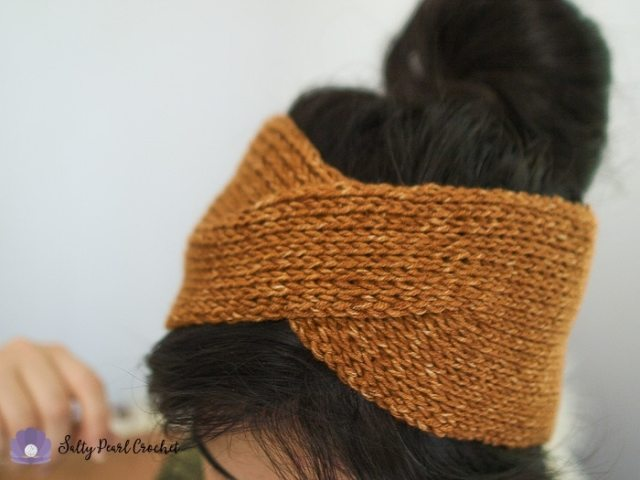 A close up of a woman wearing a crochet headwrap with a messy bun hairdo.