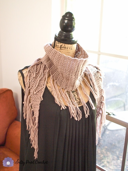 Angled view of the free crochet triangle scarf to show the fringe.