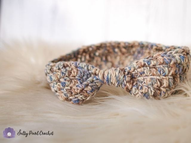 An easy to crochet ear warmer pattern sample on a furry sheepskin rug.