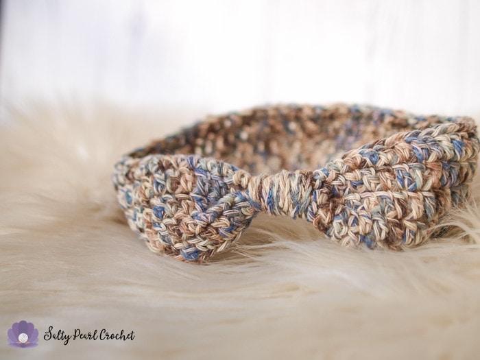 An easy to crochet ear warmer pattern sample on a furry sheepskin rug.