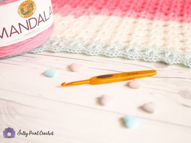 A Clover Soft Touch Crochet Hook with a candy colored crochet project.