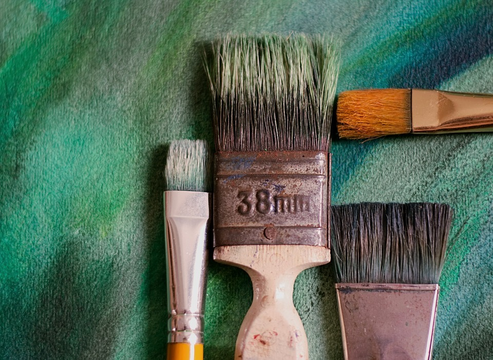 Several sturdy paintbrushes of various sizes on a teal, brush-stroked background.