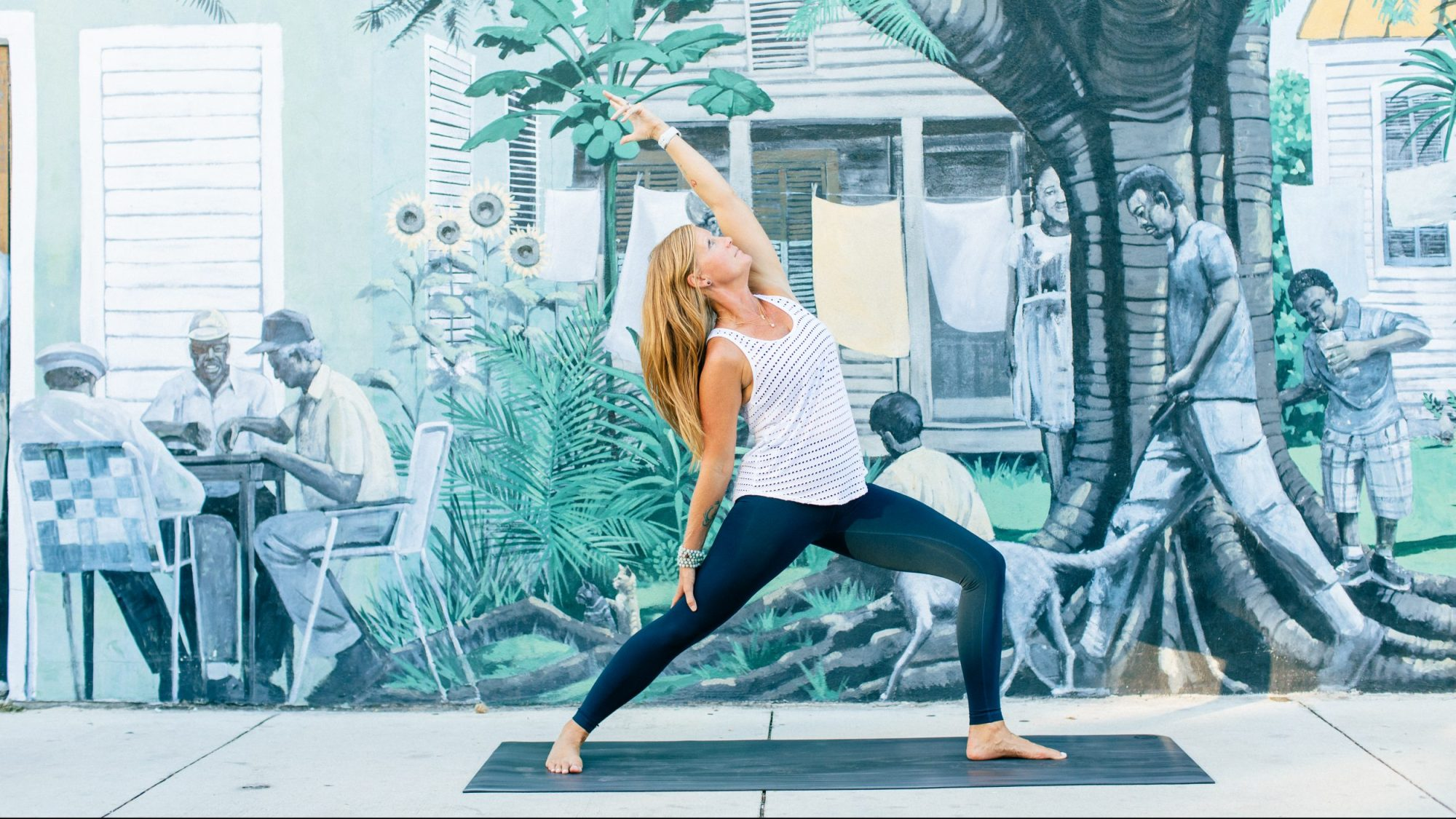 woman doing a yoga pose in front of a mural