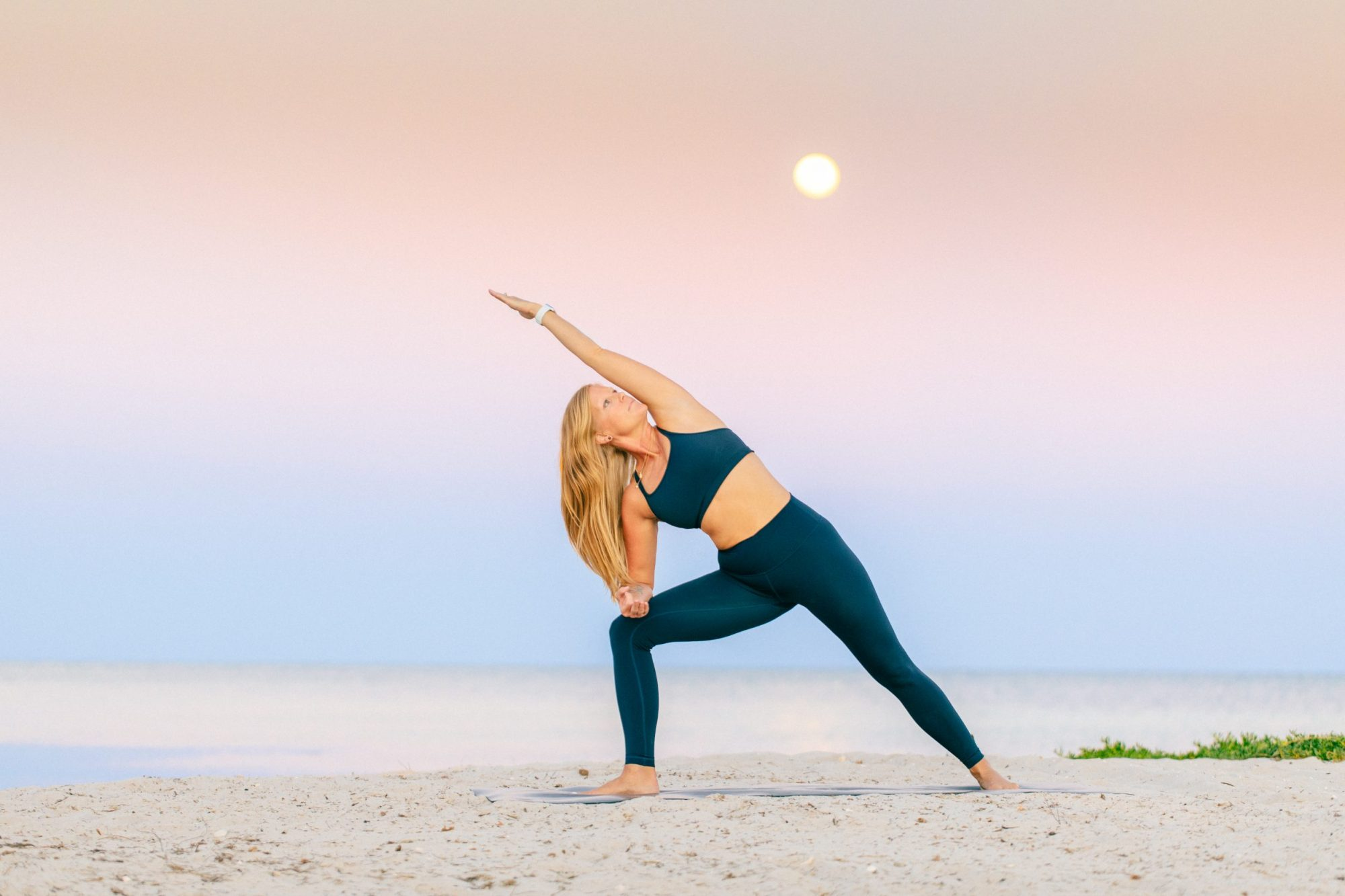 woman doing a yoga poze on the beach at sunset