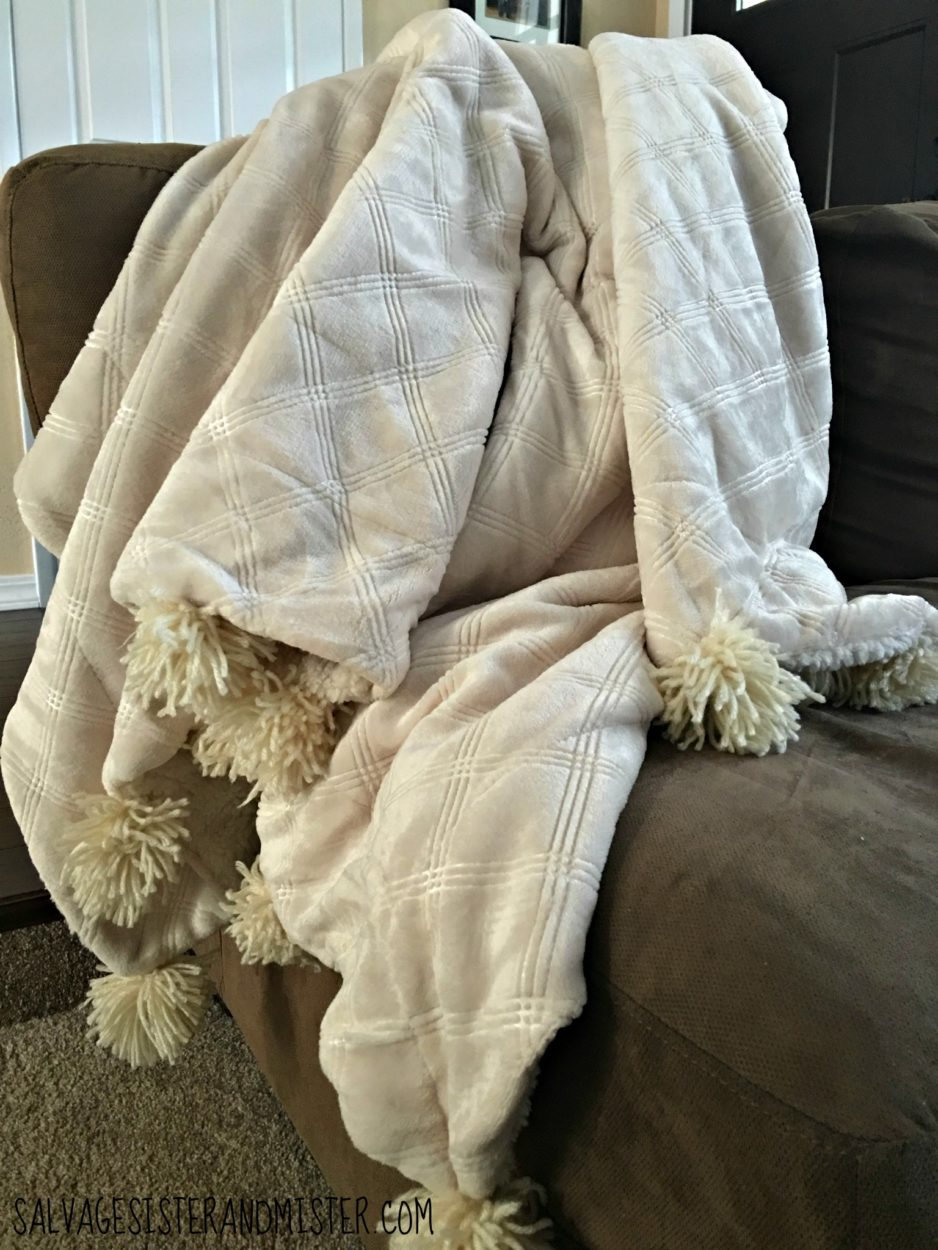 DIY pom pom blanket made from an on sale sherpa blanket and some thrift store yarn. Easy DIY project that requirres very little hand sewing.