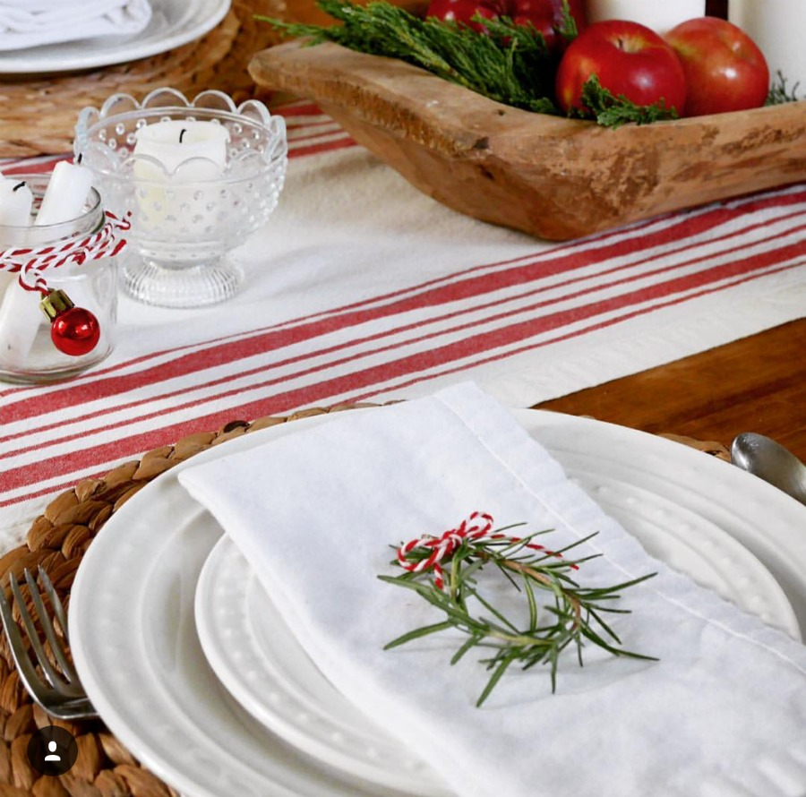With just a few items you can make a beautiful table. Here you can see rosemary sprigs, glass dish for a candle holder and a old dough bowl for a center piece. Beautiful farmhouse style. An elegant table setting using what you have and a few extra items.