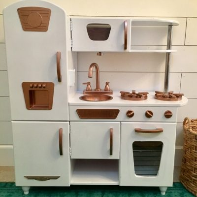 A handy me down play kitchen gets an update to match the grown up kitchen. This DIY project shows you what you need to update a thrifted or free find to a sleek new toy for your child. Kids can cook right along side of you. Play ktichen update