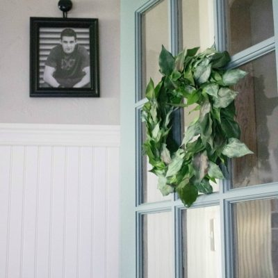 Creating a faux magnolia wreath from a fake house[plant. This easy and budget-friendly craft is great to reuse an item that might otherwise get discarded. Get the dull DIY info at salvagesisterandmister.com