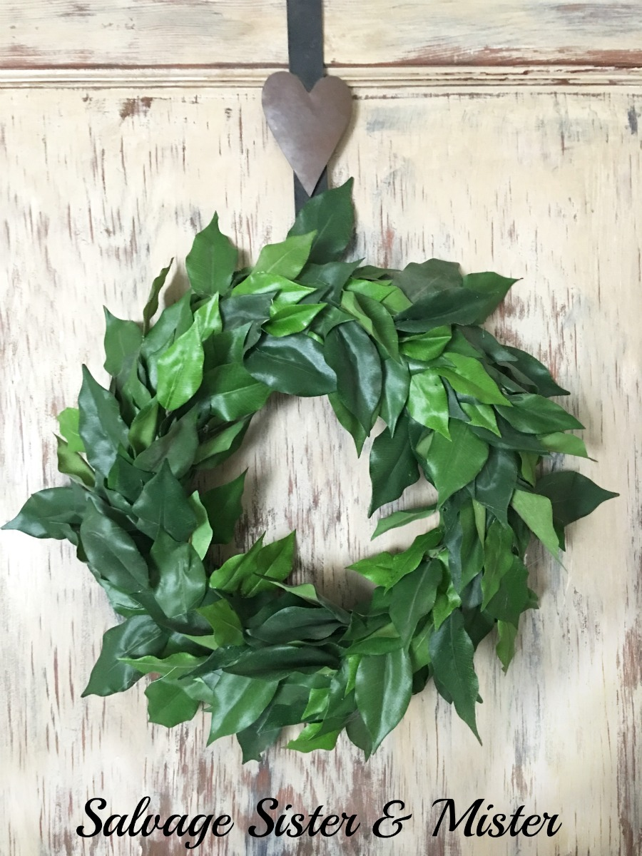 A DIY bargain faux magnolia wreath. When you can't buy one from Magnolia Market what do you do? You make one from leftover supplies for free. This craft project was easy to do and great for the farmhouse look on a dime. Perfect green for the rustic door behind. Home decor doesn't have to be expensive.