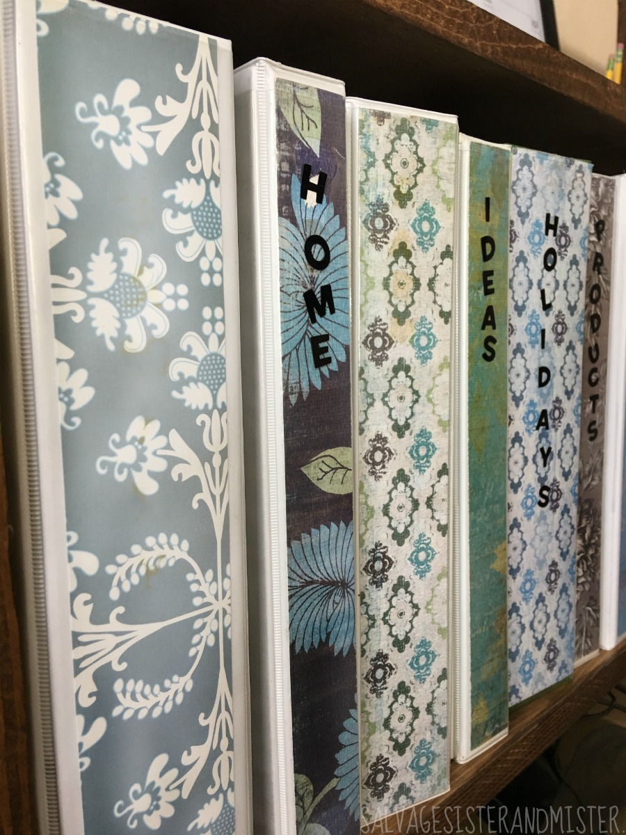 Using thrft store binders for home office organization. With a little leftover scrapbook paper these binders and now a great decor item that makes the office more appealing