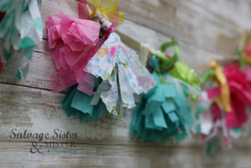 creating some party fun and using up leftover tissue paper in the process - reuse. Find out how to make this tissue paper tassel garland craft on salvagesisterandmsiter.com