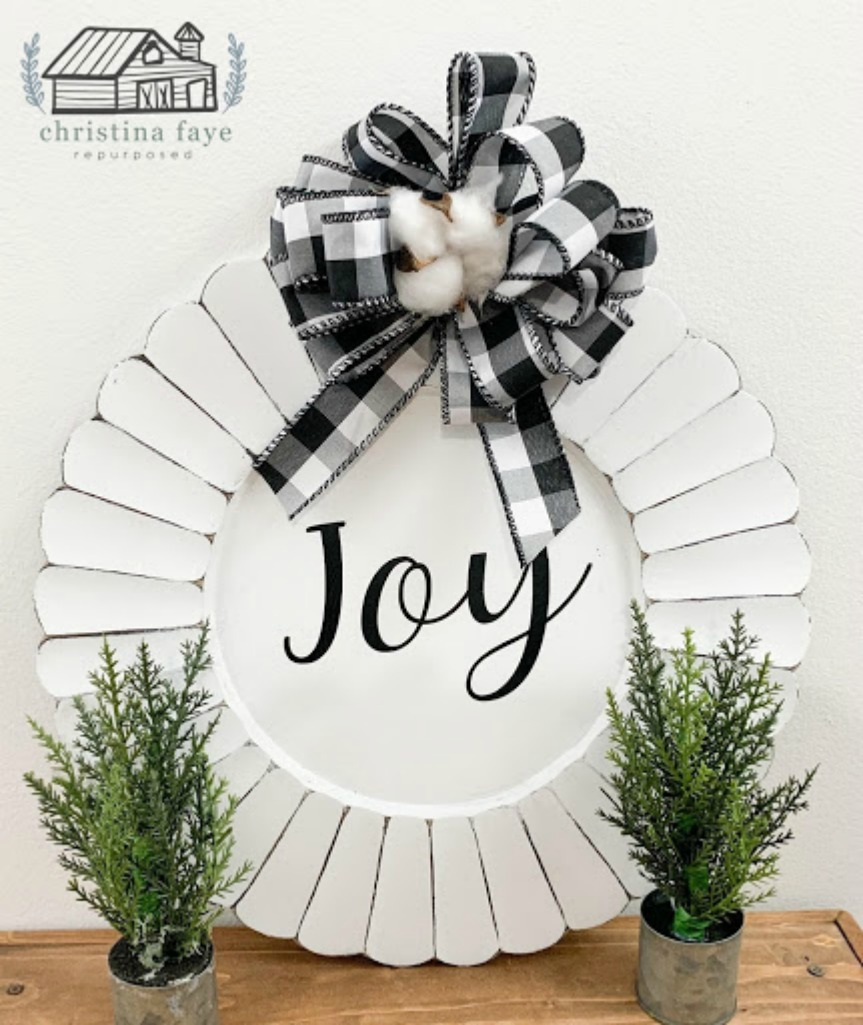 A farmhouse style thrift store transformation - charger plate Christmas craft (decoration). Inexpensive holiday decoration and easy to make. Can be done using your Cricut or other vinyl machine or a stencil. Get the full DIY instructions to repurpose a charger here at salvagesisterandmister.com