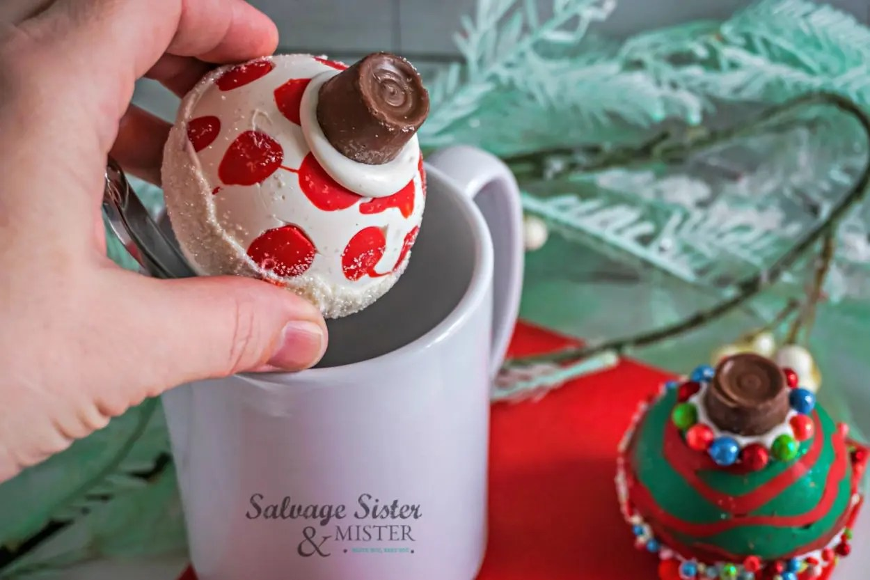 Placing Christmas ornament hot cocoa bomb in cup