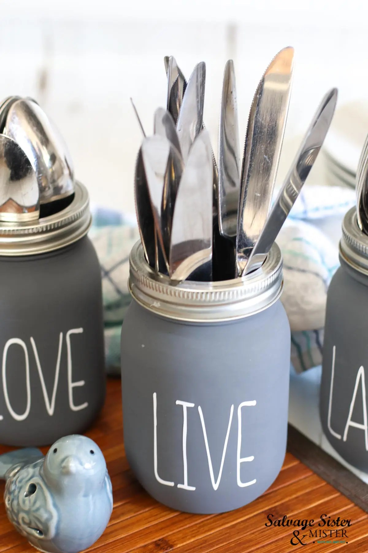 Close up view of the gray chalky paint jar mason jar with LIVE decal filled with butter knives.