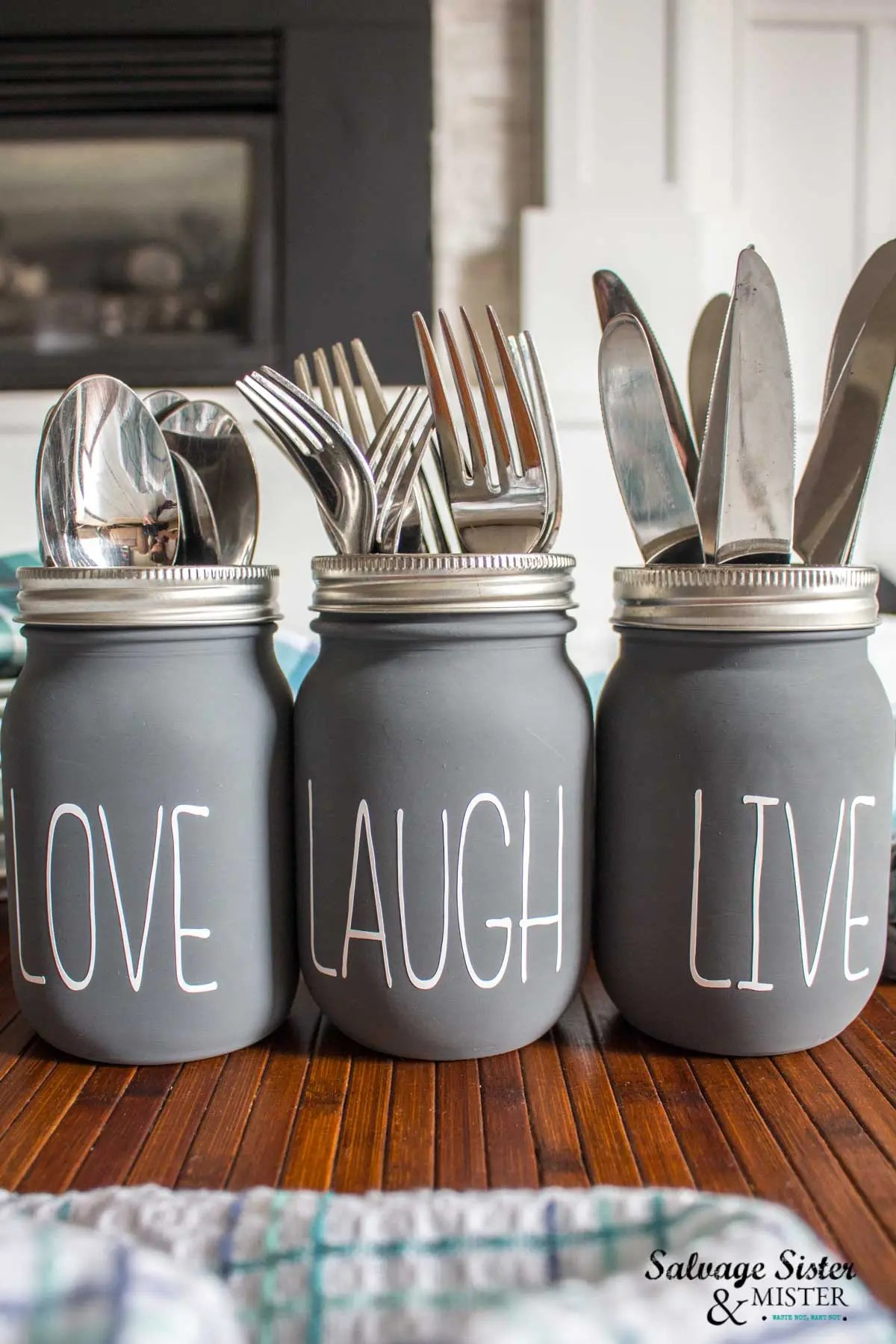 Three dark gray chalky painted mason jars with silver rims side by side on a cherry wood surface. Each jar is filled with different utensils and has white decals which say Love, Laugh and Live respectively.