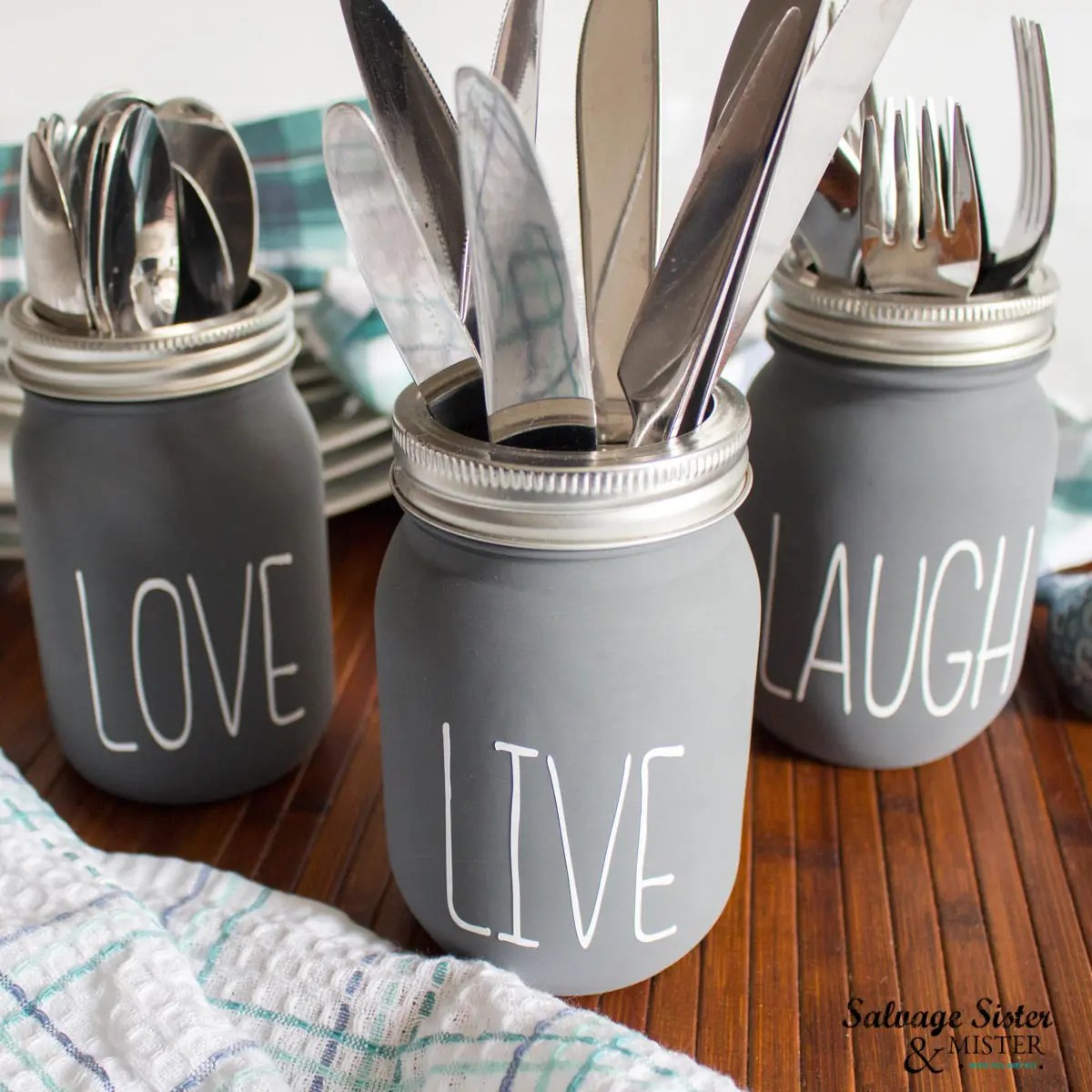 All three dark grey chalky painted mason jars with LIVE, LAUGH, LOVE decals, filled with different silverware respectively. The jars are on a cherry wood surface with tea towel in foreground and stack of plates in the background.