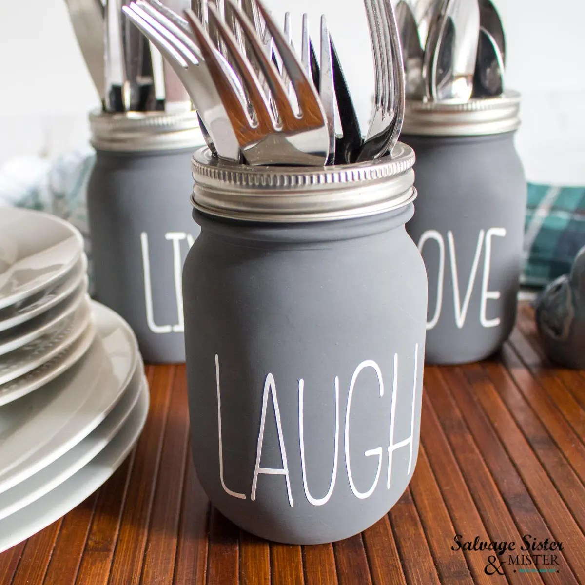Close up view of the gray painted mason jar with the phrase LAUGH in white permanent vinyl. The jar is filled with forks and the other two jars are slightly out of focus in the background.