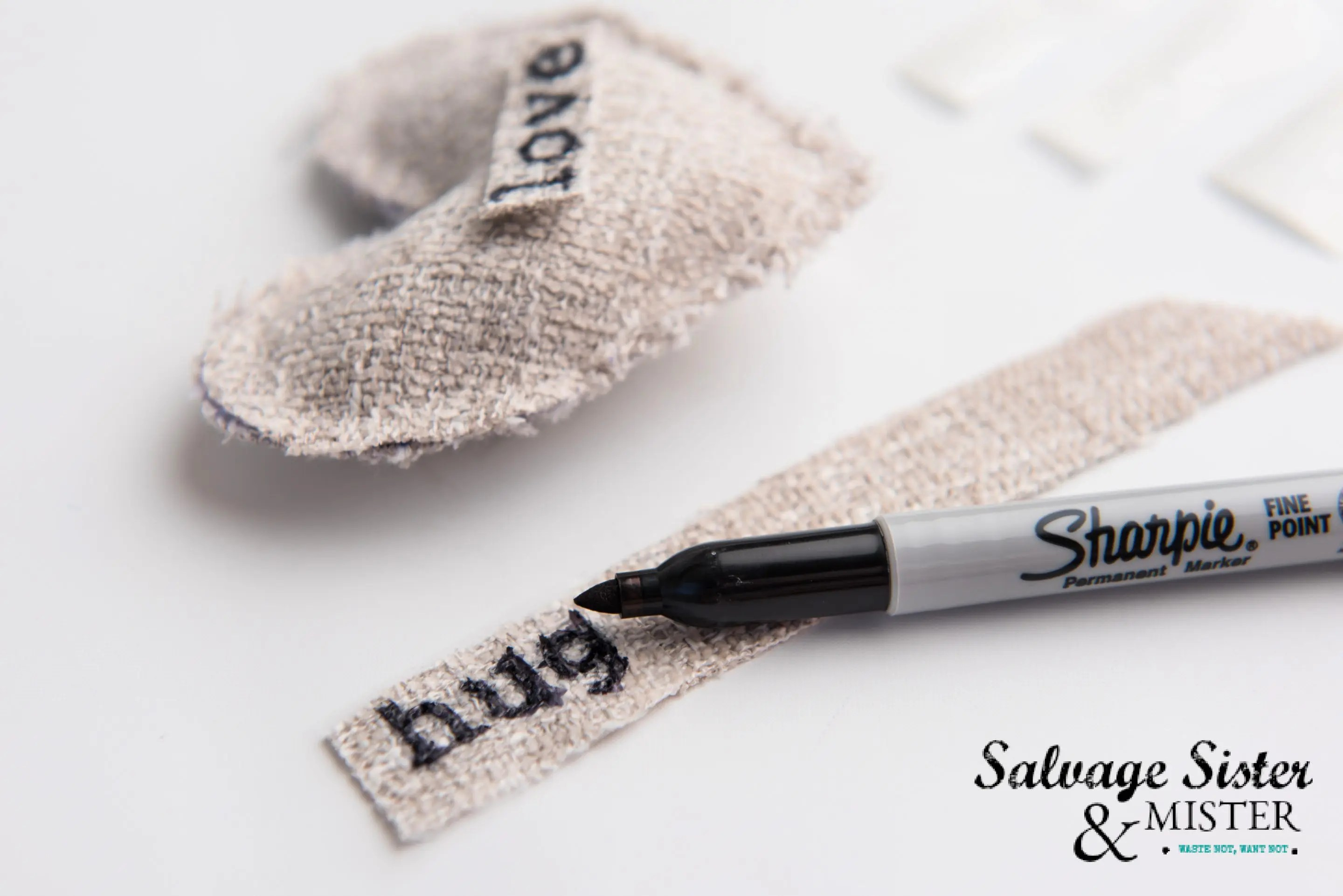 Create a stamped lettered look using a stencil and sharpie pen on burlap.