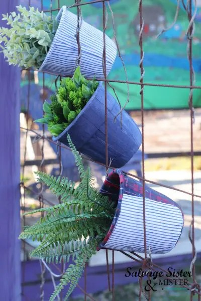 An example of how to display upcycled decoupaged planters in a wire fence.