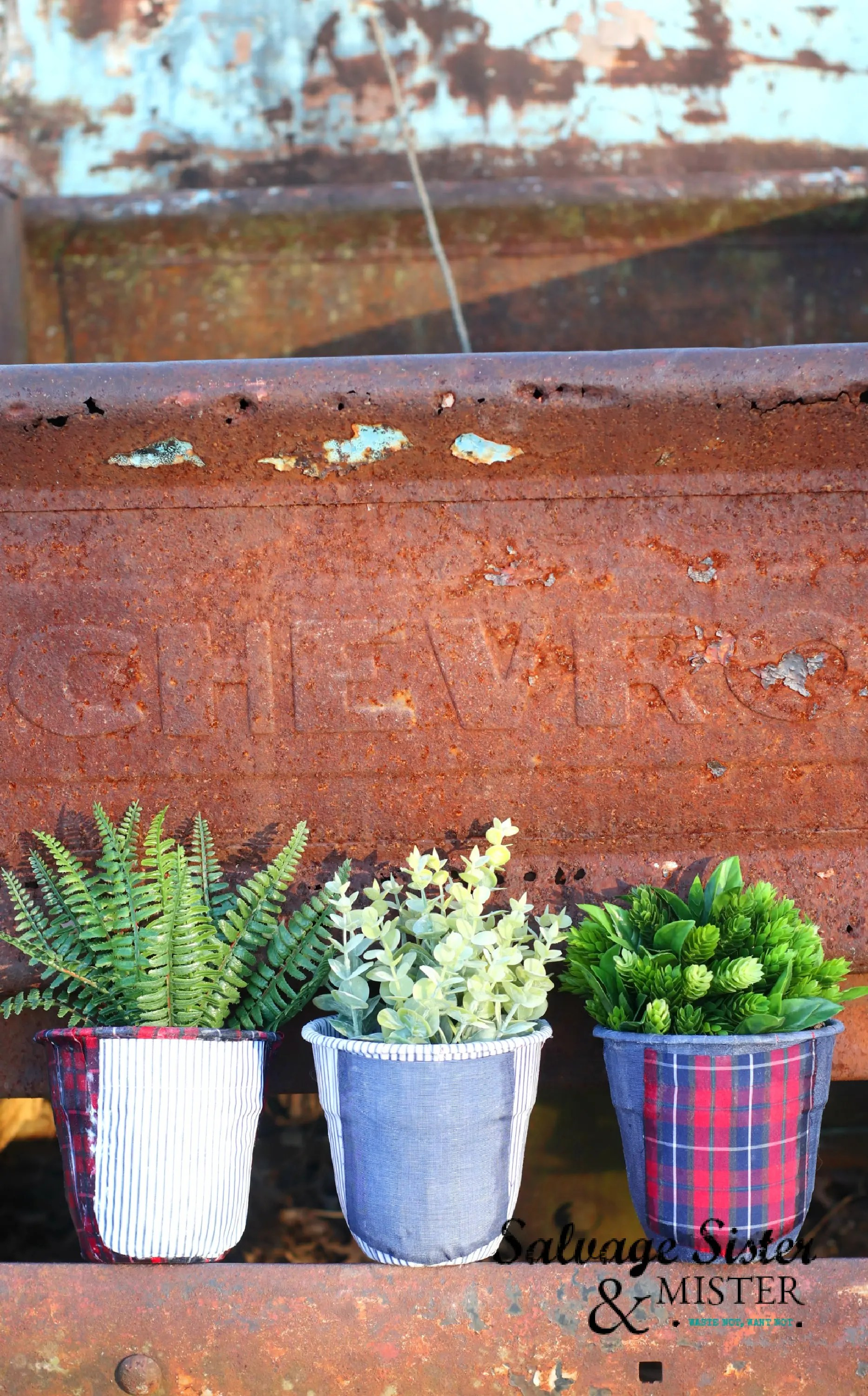 Upcycled men's shirt decoupaged planters in front of a brick wall.