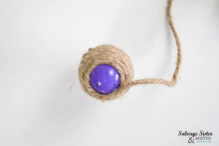 cover plastic egg completely and trim end of twine