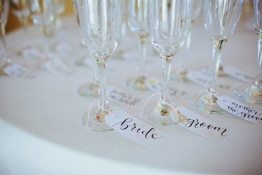 Small White Tags, Black Ink for Names with Table Numbers in Pink, Dahlia Lettering Style —Photography by Jonathan and Marie Connolly