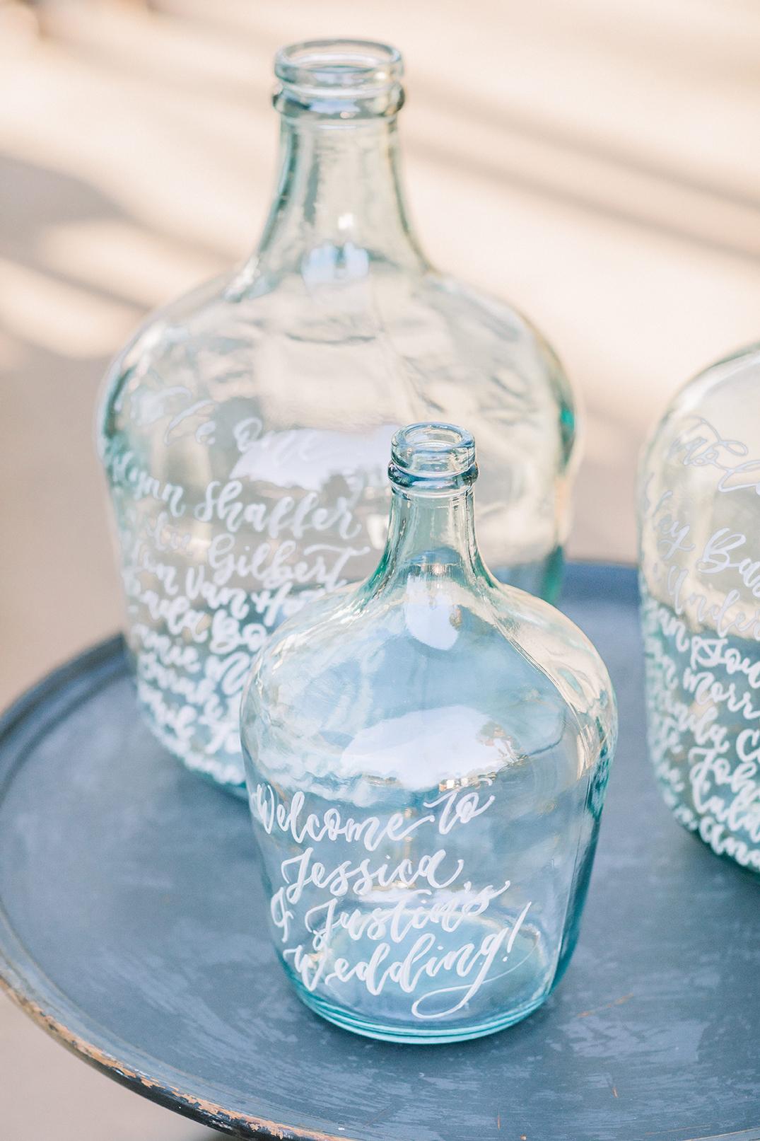 SWP-TheGreenhouse Boho Wedding Inspiration-241SWP Sam Allen Creates Seating Chart on Blue Glass Bottles