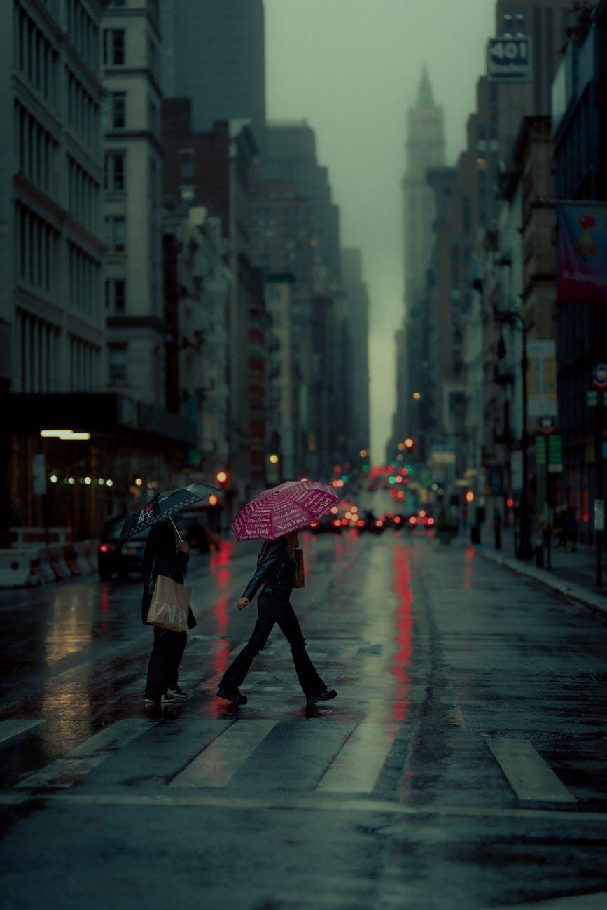 man in black jacket holding umbrella walking on street