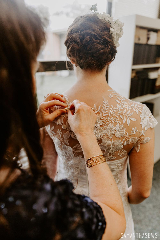 mama buttoning my handmade lace wedding dress