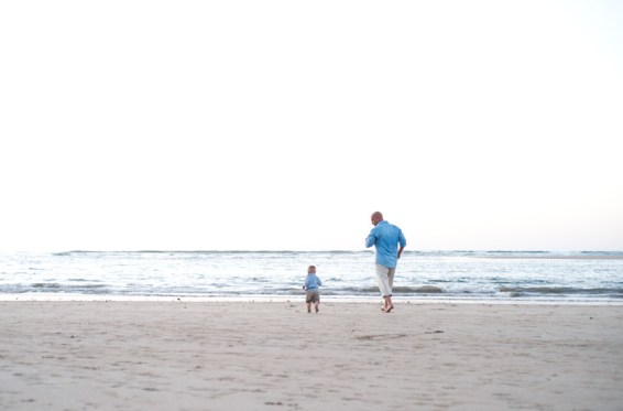 Father and young toddler sun running on the beach in Tamarindo, Costa Rica. Photographed by Kristen M. Brown, Samba to the Sea Photography.
