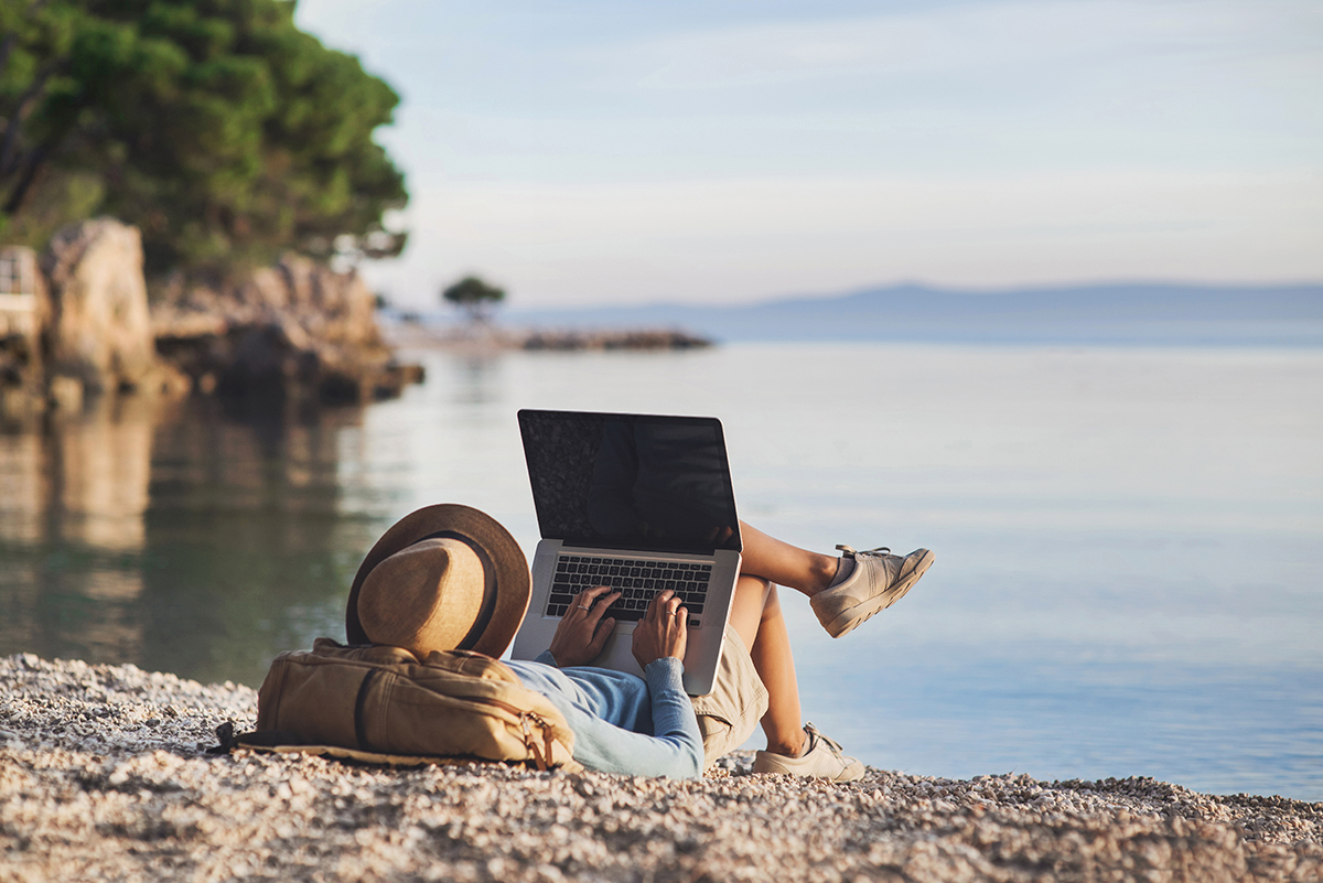 Young woman with a hat and backpack using laptop computer on a beach while laying down.