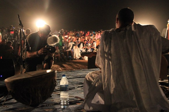 A member of Mariam Hassan's band tunes his instrument.