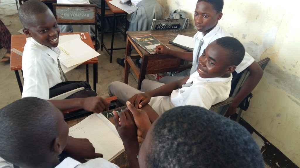 A group of five maths club members from Tande secondary school discussing the triangle puzzle.