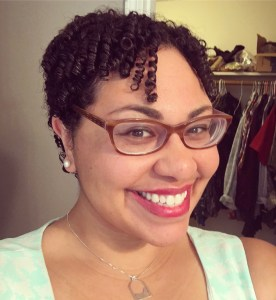 Photo of Dr. Schalk. She is a light skinned black woman with glasses and short curly hair. A few tight coils fall down her forehead. She is wearing brown glasses, pearl earrings, a mint and white sleeveless top and a silver necklace