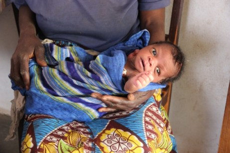 orphaned baby needing formula, cradled in granny's arms