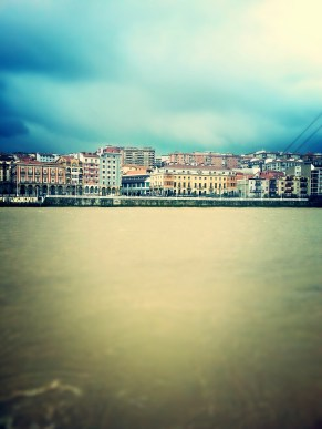 Looking at Portugalete over a brown river, the storm churns up all the sand