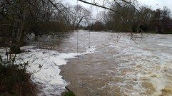 The River Stour swollen and bursting its banks