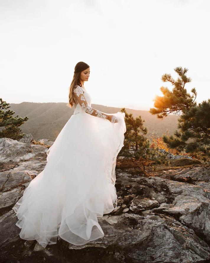 holding wedding dress as the sun sets