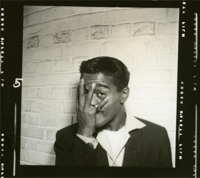 Sammy Davis Jr. covering his face with his right hand