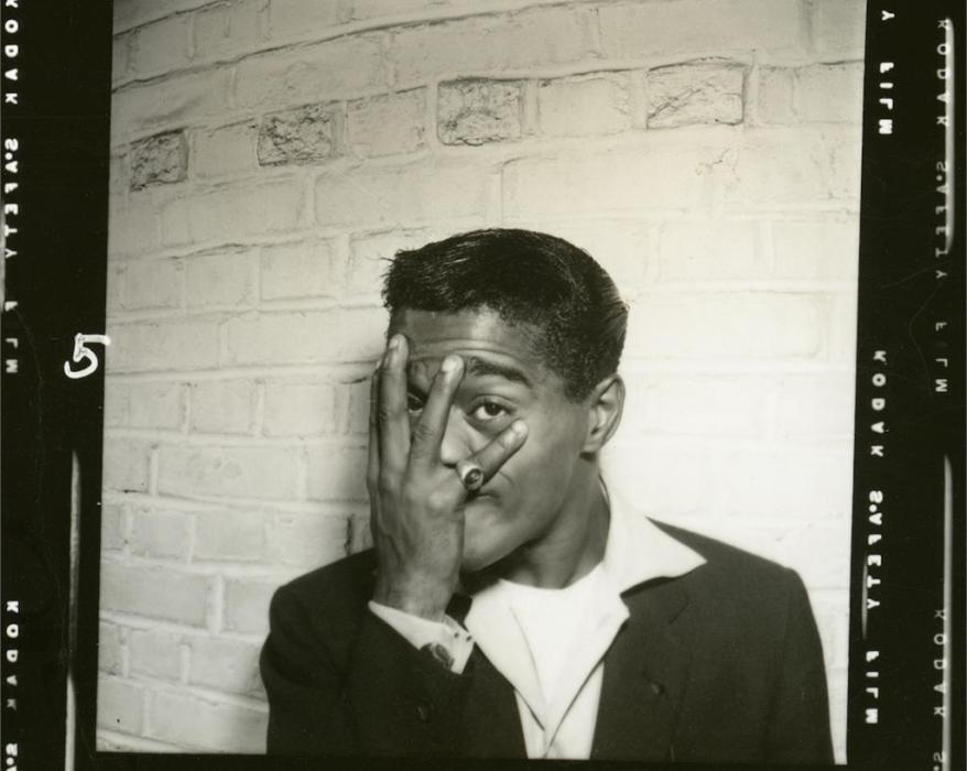 Sammy Davis Jr. covering his face with his left hand