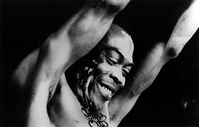 Fela Kuti smiling, with his arms in the air