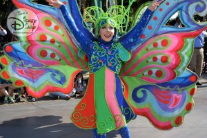 Tinker Bell followed by colorful costumes during Mickey's Soundsatonal parade.