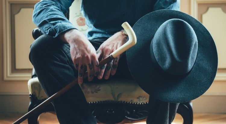 Photo of tattooed hands holding a cane and hat on samuelpavin.com