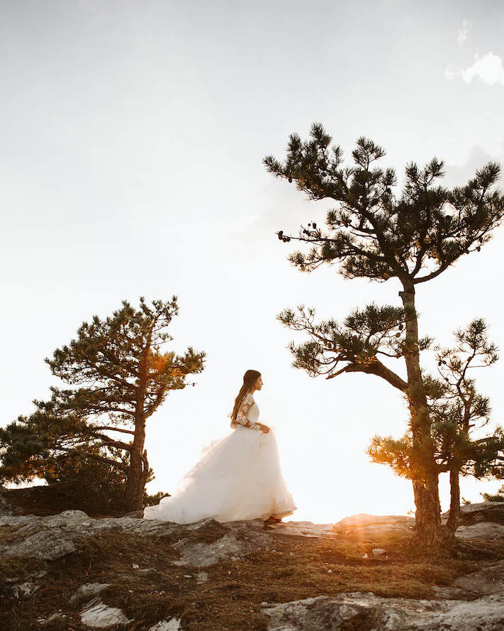 bride in her wedding dress walks across rocks while the sun beams through