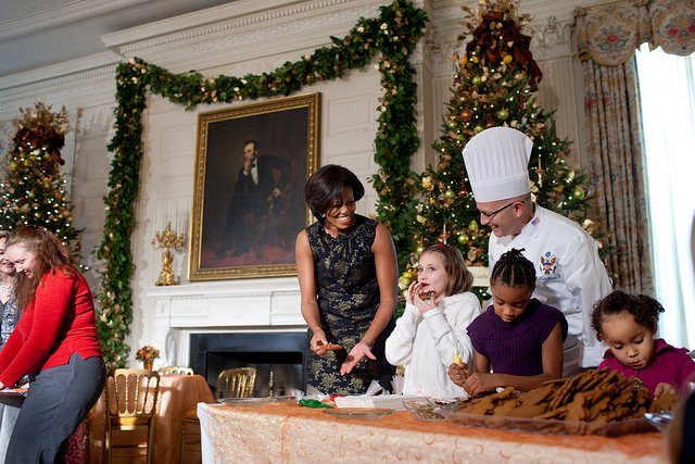 First Lady Michelle Obama and White House Pastry Chef Bill Yosses laugh as a young visitor tastes her decorated cookie with the children of military personnel in the State Dining Room. (Official White House Photo by Lawrence Jackson)