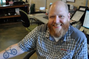 Caleb Choate shows us his tattoo at the B-cycle office. Photo by Iris Dimmick